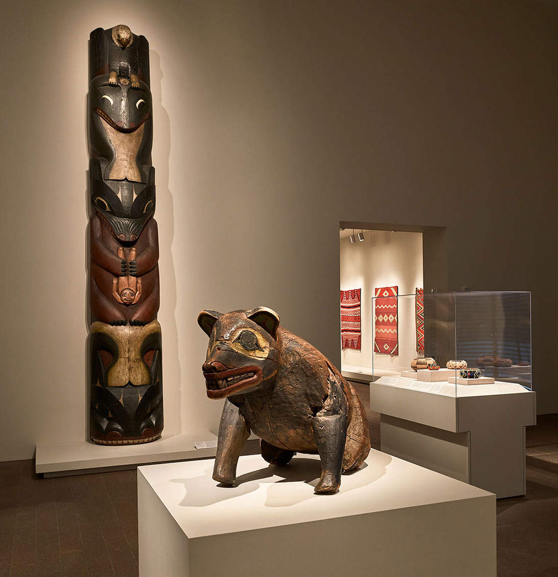 Installation view of Native Artists of Western North America showing totem pole and bear effigy