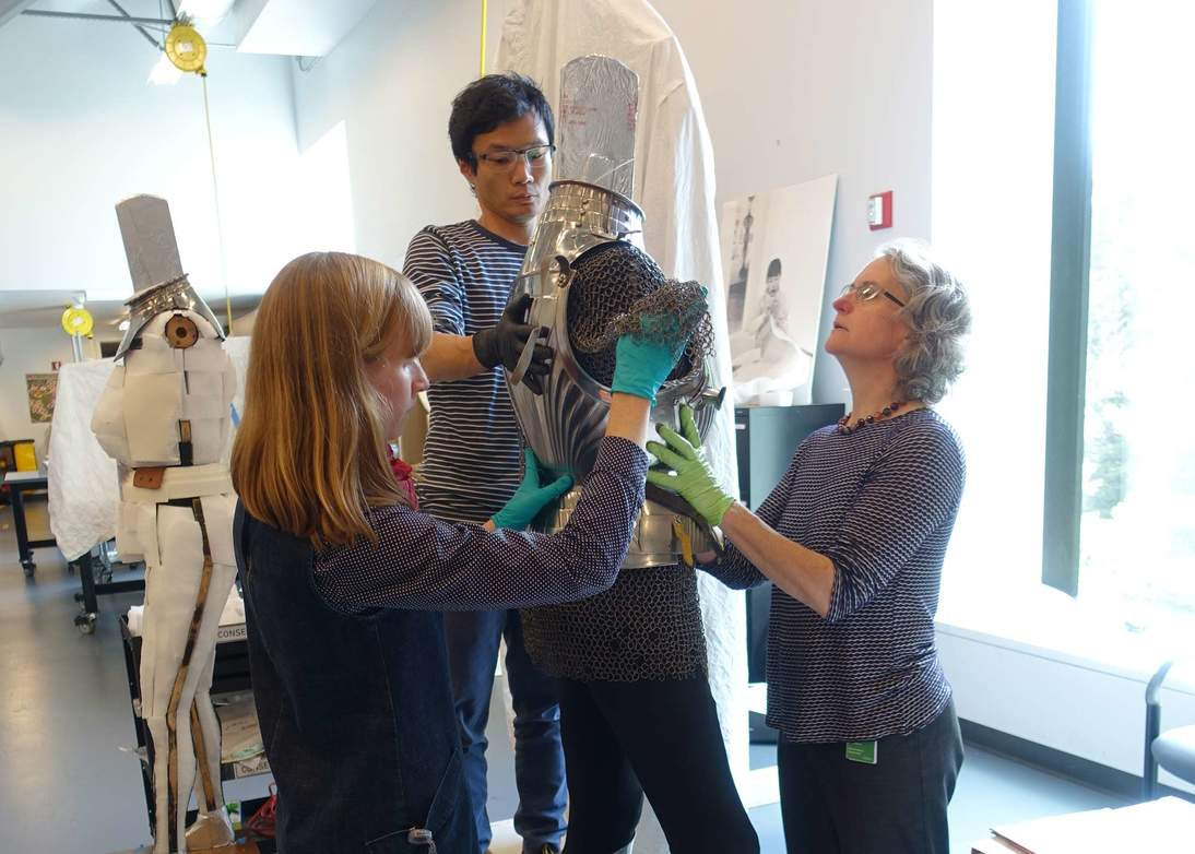 Objects conservators Colleen O'Shea and Jane Williams and mountmaker Mike Lai check the fit of the armor on its modified support and how well new mounts are supported.